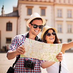 • 5 essential oils for travellers with a man and woman smiling and looking at a map (Oil images): • peppermint oil bottle • Stress away essential oil bottle • Digize essential oil bottle • Lavender oil bottle