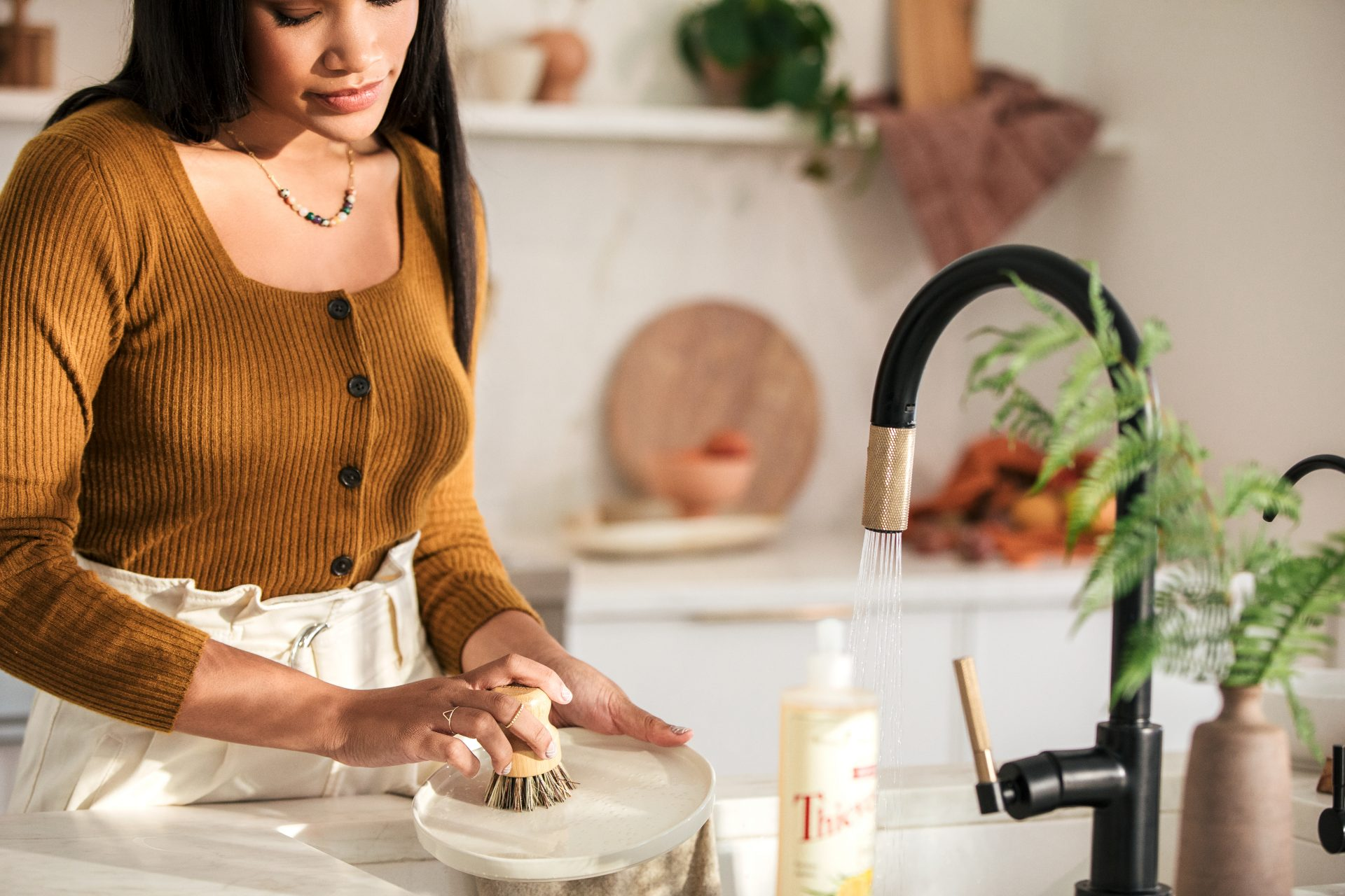 Woman washing dishes using Young Living Essential Oils Thieves dishsoap