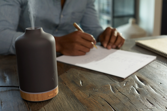 Man making a to-do list with the Young Living ember diffuser near by