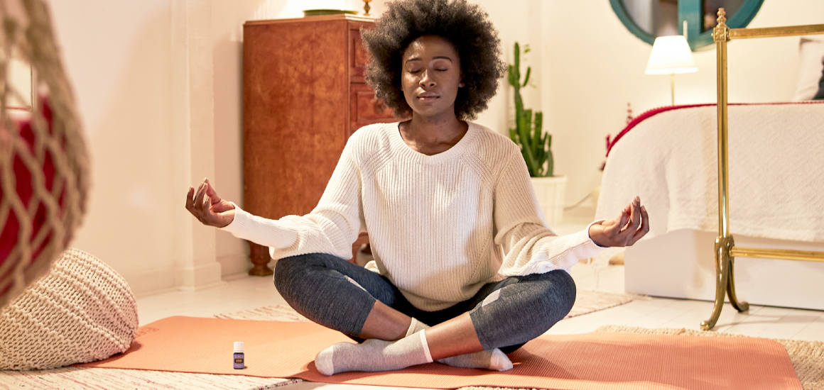 Woman meditating with Young Living essential oil RutaVala