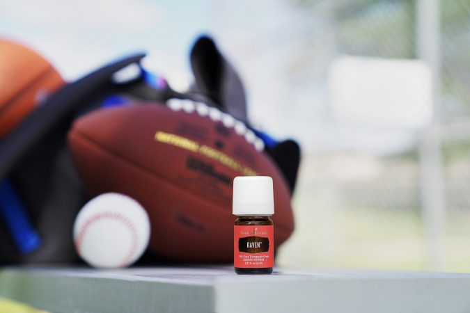 A bottle of raven essential oil with sports equipment, use raven essential oil after exercising or playing sports