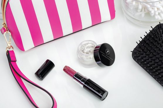 savvy minerals lip scrub and savvy minerals lipstick in a shade of pink with a pink and white striped cosmetic bag