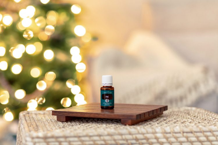 a bottle of pine essential oil in front of a glowing christmas tree