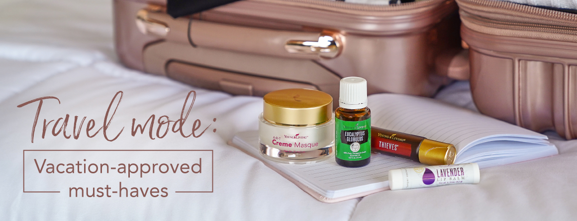 An open suitcase packed with clothes and essential oil products for travel: Breathe again roll on, eucalyptus globulus essential oil, and ART creme masque