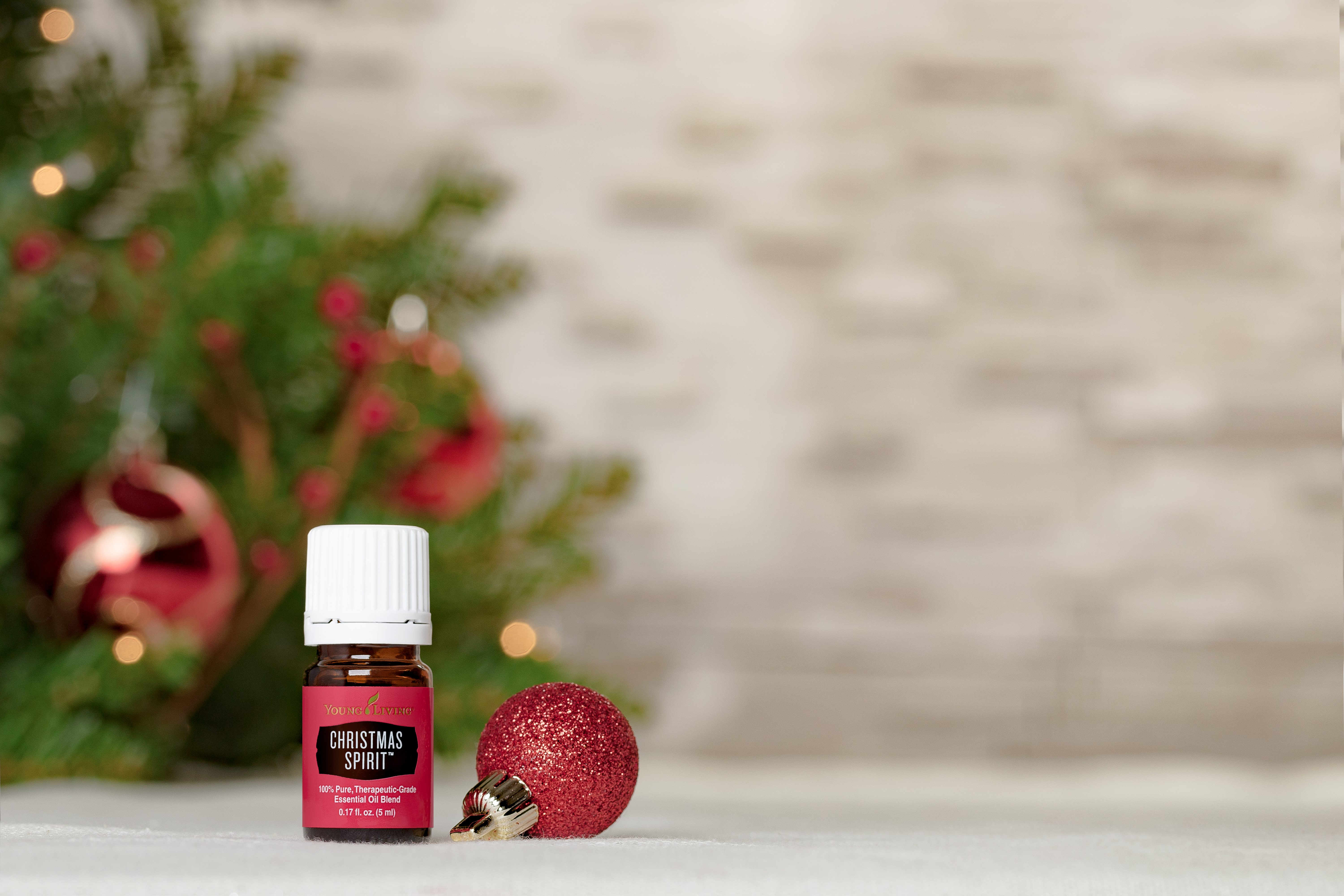 christmas spirit essential oil in front of a festive christmas tree