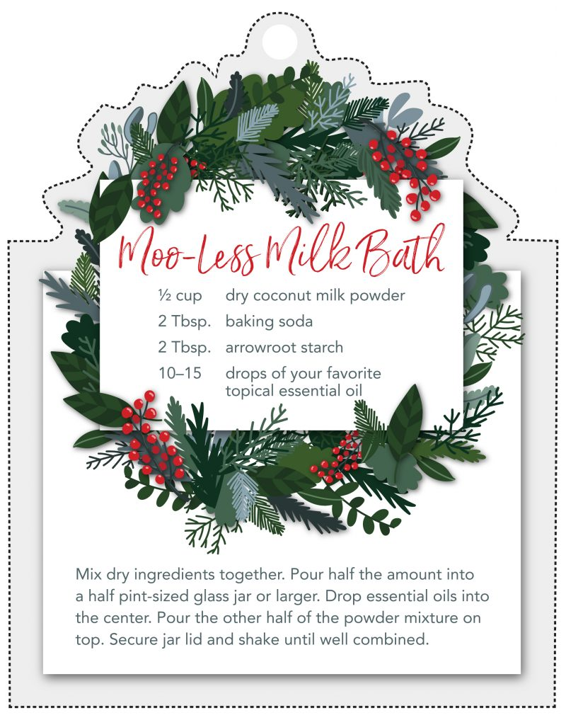 Moo-less milk bath printable gift tag showing a festive wreath and the recipe. Moo-less milk bath recipe: 1/2 cup dry coconut milk powder, 2 tablespoons baking soda, 2 tablespoons arrowroot starch, 10 to 15 drops of your favorite topical essential oils. mix dry ingredients together. pour half the amount into a half pint-sized glass jar or larger. drop essential oils into the center, pour the other half of the powder mixture on top. secure jar lid and shake until well combined.