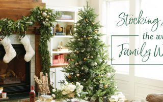 "a festive living room with stocking stuffer ideas, decorated for christmas with a tree, stockings, and presents. Corner text says: ""Stocking stuffers the whole family will love!"""