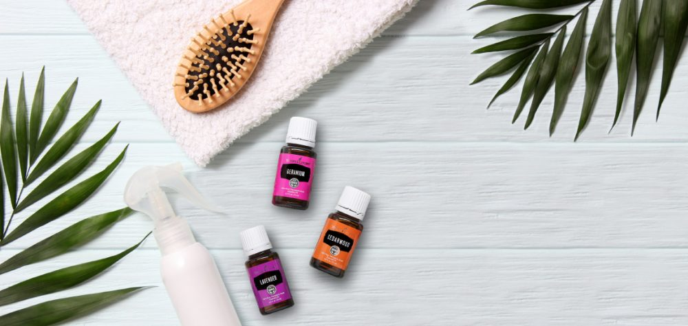 Essential oils for hair on bathroom surface with brush and towel
