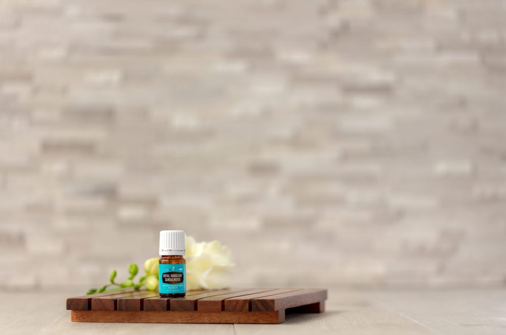 royal hawaiian sandalwood essential oil on a wood platform in front of a tile background