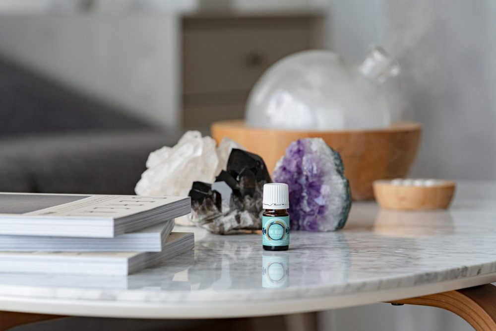 one heart essential oil blend on a table with crystals and a diffuser