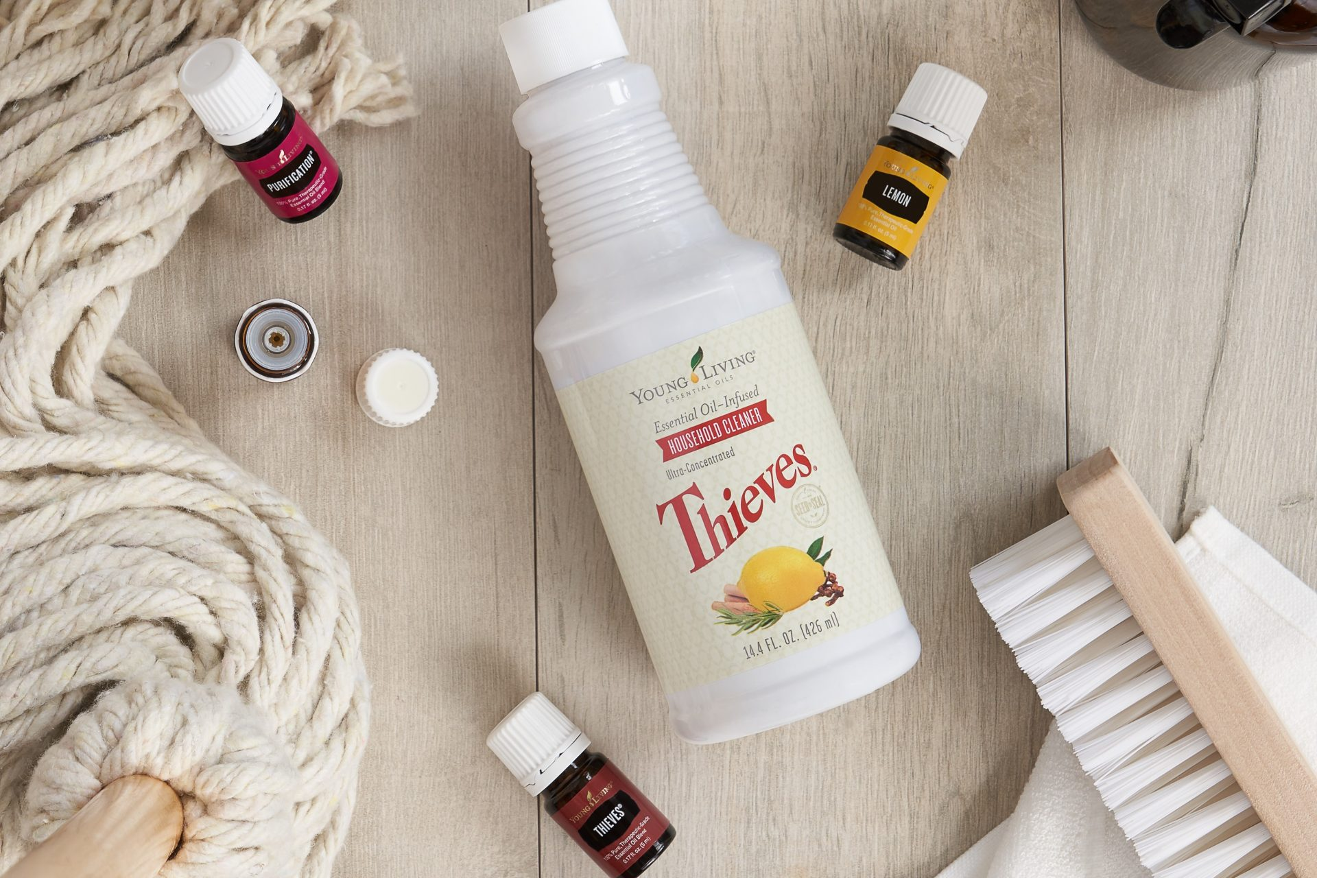 Thieves household cleaner, purification, thieves, aand lemon essential oils surrounded by cleaning supplies