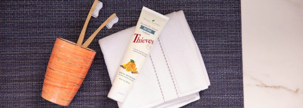 Thieves whitening toothpaste with a tooth brush and washcloth on a counter