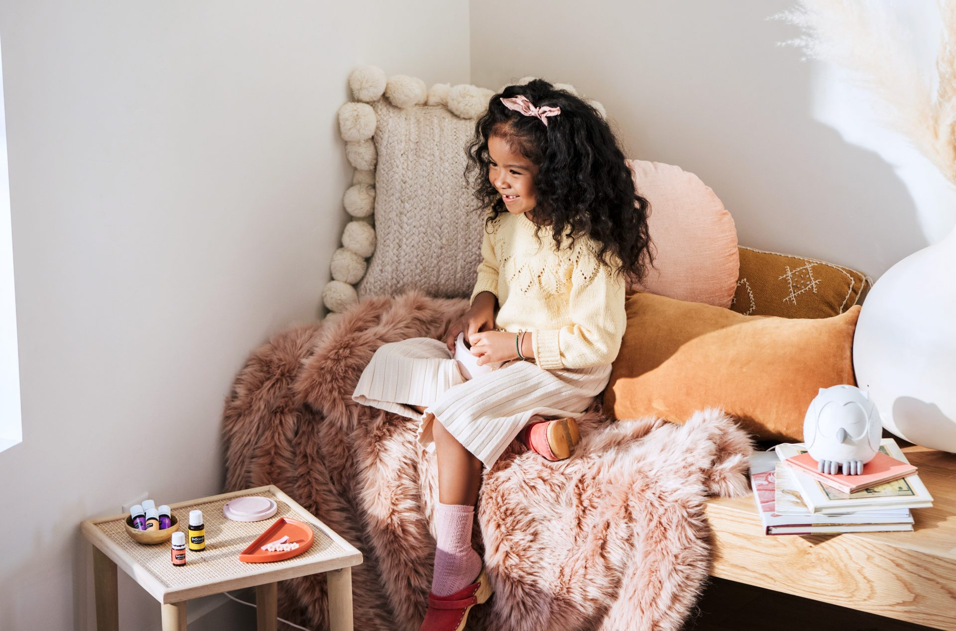Young girl with young living essential oil and diffuser