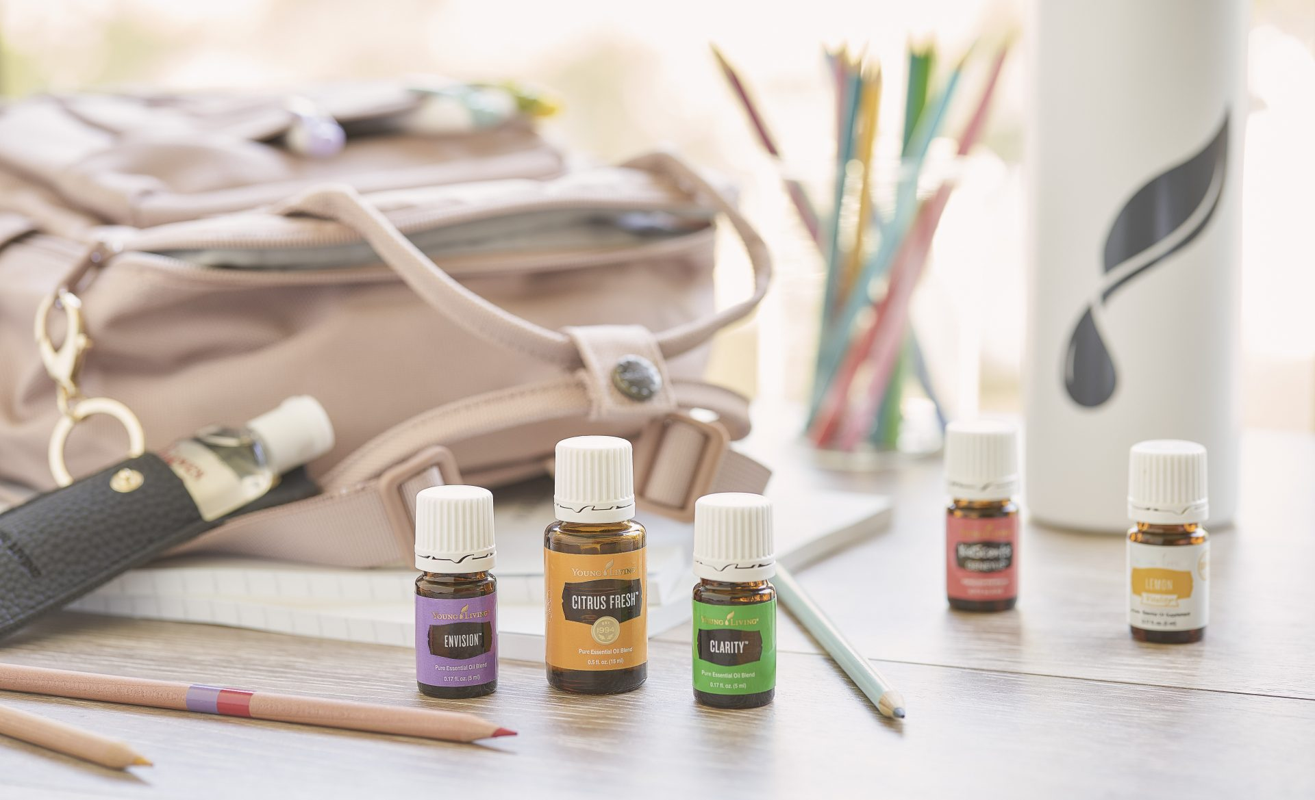 Envision, Citrus Fresh, Clarity, KidScents GeneYus, and Lemon Vitality essential oils surrounded by a backpack, YL Gear Drop bottle, Madison hand sanitizer holder, and other school supplies - Young Living Lavender Life Blog
