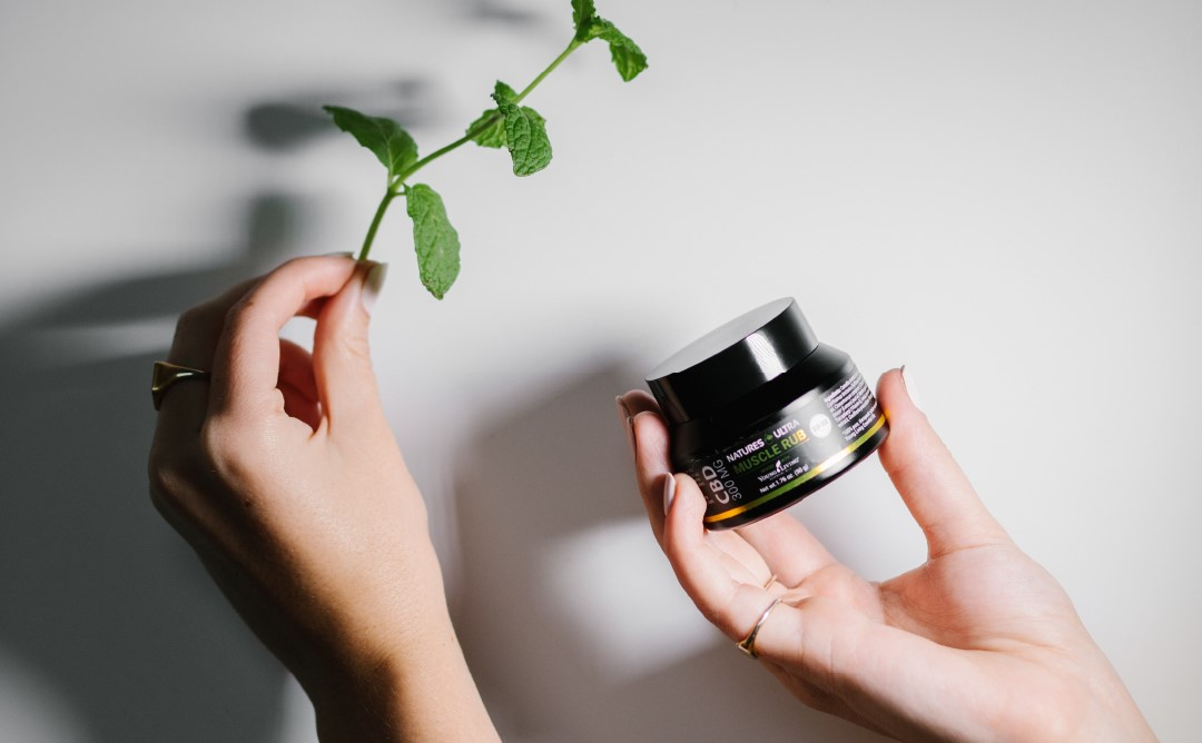 Hands holding CBD Muscle Rub and mint leaf - Young Living Lavender Life Blog